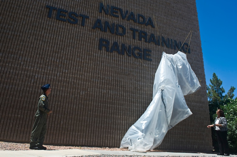 U.S. Air Force Col. Kenneth Thompson, Nevada Test and Training Range commander, and Mrs. Yvonne Gresnick, NTTR deputy director, unveil the new NTTR building sign at Nellis Air Force Base, Nev., after 98th Range Wing was officially re-designated the NTTR June 21, 2011.  Like the 98 RANW, The NTTR will remain a direct reporting unit to the U.S. Air Force Warfare Center and continue to operate, maintain and manage the 2.9-million-acre range (42 percent of the land managed by the U.S. Air Force) and 12,000 square miles of military airspace. More than 1,000 military, civilian and contract personnel are assigned to the organization. (U.S. Air Force photo by Senior Airman Brett Clashman/Released)