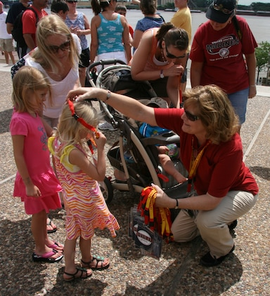 Gloria Pryor of Marine Corps Systems Command's Corporate Communications Directorate gives a child a Marine Corps lanyard during Marine Week St. Louis.