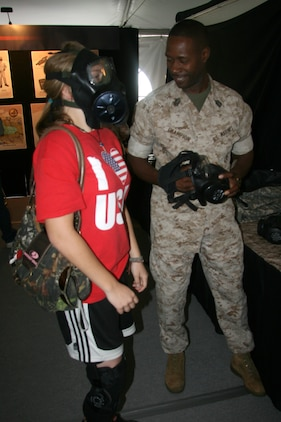 A Marine Week St. Louis visitor tries on an M50 Field Protective Mask with the help of Master Sergeant Eugene Champion of Marine Corps Systems Command's Combat Equipment and Support Systems.