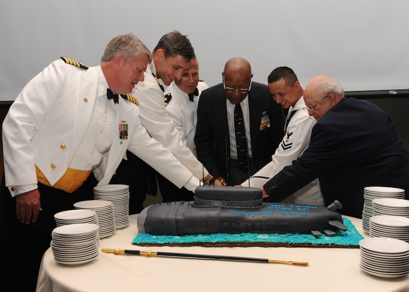 "Charleston area submariners recently celebrated 111 years of service at the Submarine Ball June 18 at Trident Technical College's banquet facility. Cutting the ceremonial cake (left to right) are Capt. Tom Bailey, Capt. Ralph Ward, Cmdr. Mark Schmitt, World War II veteran William Jones, Yeoman Second Class Flores and WOrld War II veteran Stacy Powers. Captain Bailey is the Naval Nuclear Power Training Command commanding officer, Captain Ward is the Joint Base Charleston deputy commander and Commander Schmitt is the director of Nuclear Field ""A"" school. YN2 Flores was the youngest submarine qualified member in attendance."