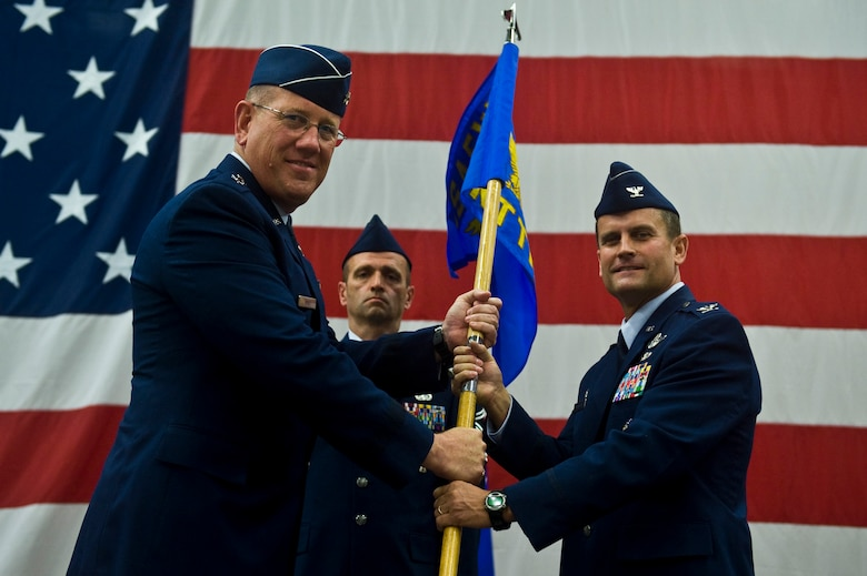 U.S. Air Force Maj. Gen. Bill Hyatt, U.S. Air Force Warfare Center commander, passes the Nevada Test and Training Range guidon to Col. Kenneth Thompson, during an assumption of command at Nellis Air Force Base, Nev., June 21, 2011. During the event, the 98th Range Wing was officially re-designated the NTTR and will remain a direct reporting unit to the U.S. Air Force Warfare Center. The NTTR will continue to operate, maintain and manage the 2.9-million-acre range (42 percent of the land managed by the U.S. Air Force) and 12,000 square miles of military airspace. More than 1,000 military, civilian and contract personnel are assigned to the organization. (U.S. Air Force photo by Senior Airman Brett Clashman/Released)