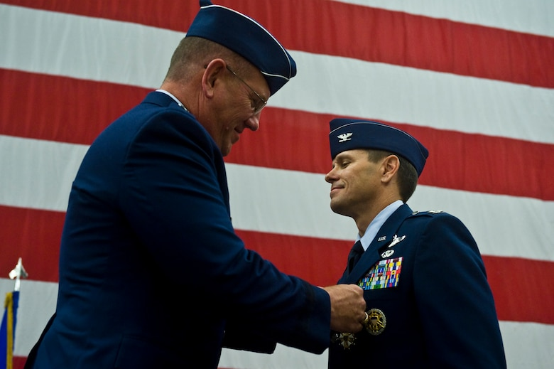 Maj. Gen. Bill Hyatt, U.S. Air Force Warfare Center commander, presents the Legion of Merit to Col. John Montgomery, 98th Range Wing commander, at Nellis Air Force Base, Nev., June 21, 2011. Colonel Montgomery had served as 98 RANW commander since July 8, 2009 and was recognized for his leadership in providing the nation's premier integrated tactics, testing, and training battlespace to U.S. Air Force, joint and coalition warfighters.  During his tenure, Colonel Montgomery led 1,000 active-duty, civilian and contact personnel who were responsible for an $87 million annual budget and electronic combat instrumentation valued in excess of $500 million. (U.S. Air Force photo by Senior Airman Brett Clashman/Released)