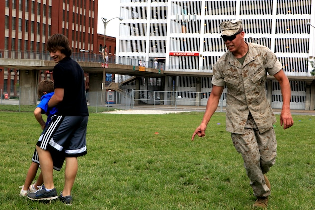 Lance Cpl. Rudy Basaldua, a machine gun team leader with 3rd Battalion, 24th Marine Regiment, directs Trevor Erickson, 13, a native of St. Louis, in the buddy drag portion of the Combat Fitness Test June 23, 2011. Locals were invited to participate in the CFT as part of Marine Week St. Louis activities.