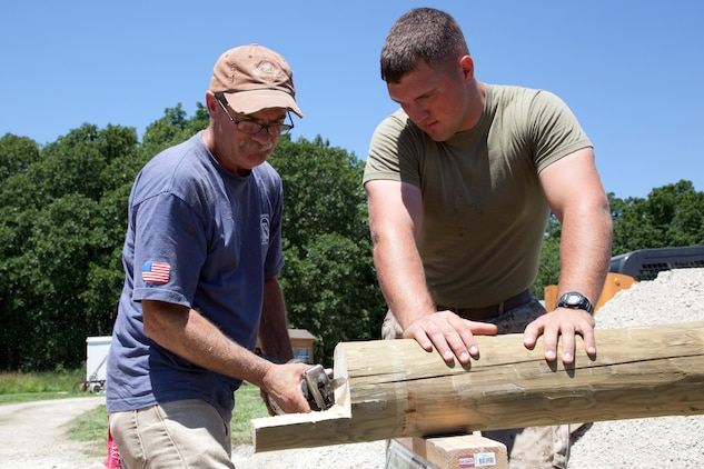 Cpl. Matthew J. Light, a granadier with Company I, 3rd Battalion, 24th Marine Regiment, Special Purpose Marine Air Ground Task Force Marine Week holds an 8-foot cedar log while a civilian volunteer cuts a notch in the log so it can be used for a fence. Marines volunteered with the Multiple Sclerosis Society to make Dauwalters farm more accessible from her wheelchair. Marine Week provides an opportunity to increase public awareness of the Marine Corps' value to our nation's defense and to preserve and mature the Corps' relationship with the American people. ::r::::n::