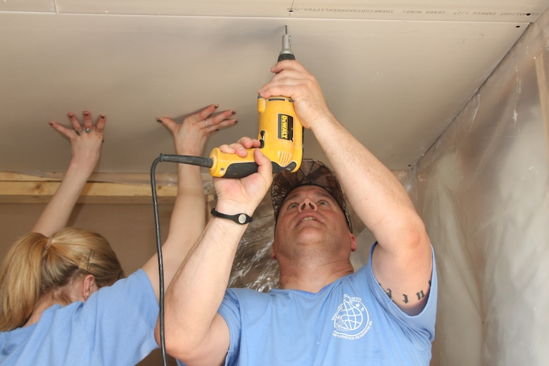 Maj. Steve Botsford (right), commander of the 128th Force Support Squadron, Milwaukee, uses a power drill to attach a drywall panel to the ceiling of a home under construction on Saturday, June 4, 2011.  Botsford, along with other Airmen from the 128th Air Refueling Wing, volunteered to help renovate houses with Habitat for Humanity.  (U.S. Air Force photo by Master Sgt. Kenneth Pagel / Released)