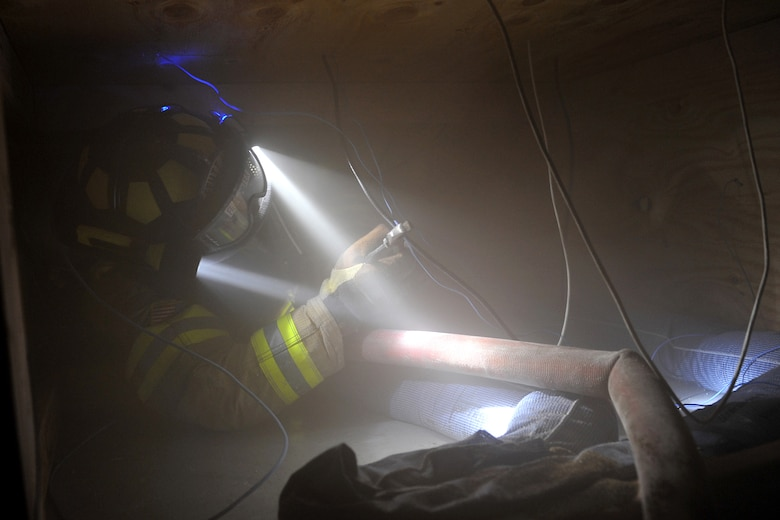 Matthew Croteau, firefighter with the 55th Civil Engineering Squadron, clips wires during the Surviving the Fire Ground, Fire Fighter/Fire Officer and Command Preparedness exercise inside building 163 on Offutt Air Force Base, Neb., June 22. Mr. Crouteau was one of 48 firefighters who participated in this training exercise. 