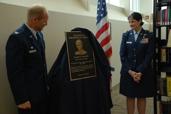 Colonel Christian Benjamin, Commander, United States Air Force School of Aerospace Medicine (USAFSAM), and Colonel Karen Weis, Dean, USAFSAM, unveil a plaque at the dedication of the school's Franzello AeroMedical Library at Wright-Patterson Air Force Base, Ohio. The library is named in honor of Joseph Franzello, a former director of the library.