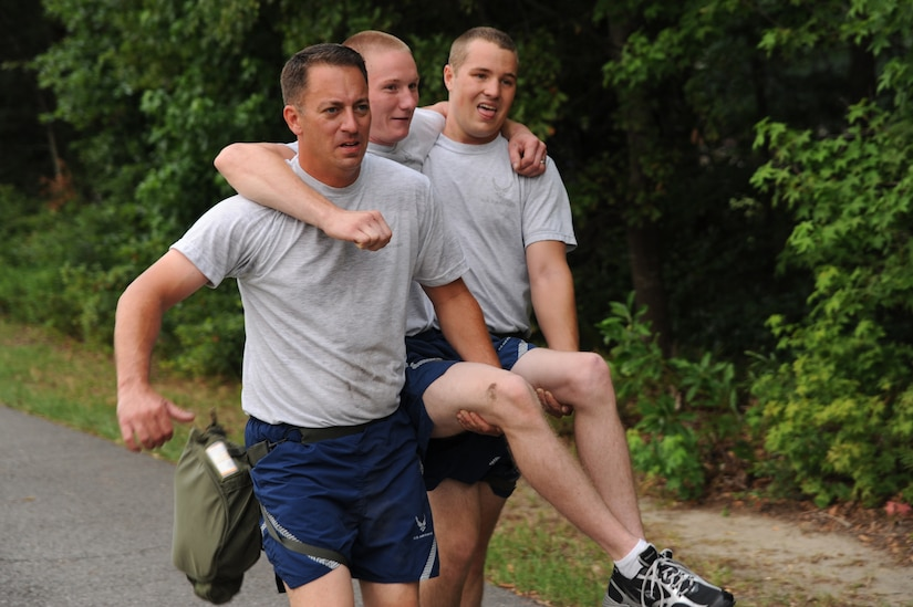Tech. Sgt. Johnathan Smiddy and Senior Airman Richard Douglas carry Senior Airman Dylan Sanford June 22 at Joint Base Charleston. Members from the 437th Aerial Port Squadron and the 437th Aircraft Maintenance Squadron meet every Wednesday to prepare for the 2011 Air Mobility Command Rodeo July 23 - 29 at Joint Base Lewis-McCord, Wash.  Sergeant Smiddy, Airman Douglas and Airman Sanford are from the 437 AMXS.  (U.S. Air Force photo/Staff Sgt. Nicole Mickle)