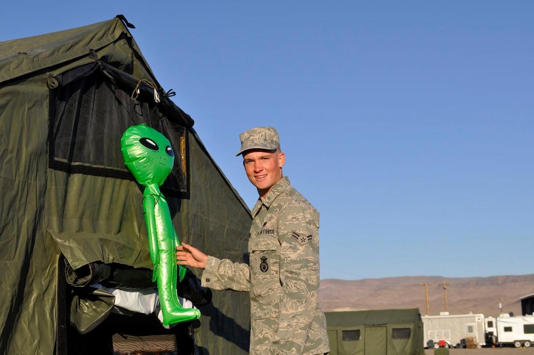"Airman 1st Class Richard Sharber with the 152AW/SF mascot ""Bob."""