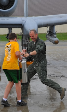 SPANGDAHLEM AIR BASE, Germany – Nate Fox, sprays water on his father, Col. Jackson Fox, 52nd Operations Group commander, after his final flight here June 24. Colonel Fox celebrated his last A-10 Thunderbolt II flight at Spangdahlem Air Base with family, friends and coworkers before taking command of the 39th Air Base Group at Incirlik Air Base, Turkey. (U.S. Air Force photo/Airman 1st Class Dillon Davis)