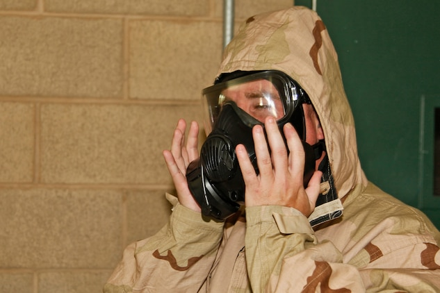 Petty Officer 1st Class Edward S. Debaun, religious program specialist, 15th Marine Expeditionary Unit (MEU), blocks the air filters on his gas mask during the Mask Confidence Exercise, an annual gas chamber training, conducted at the 33 Area Gas Chamber, June 28. Debaun, a 33-year-old native of Copperopolis, Calif., currently serves as both the religious program specialist and the acting chaplain for his unit.