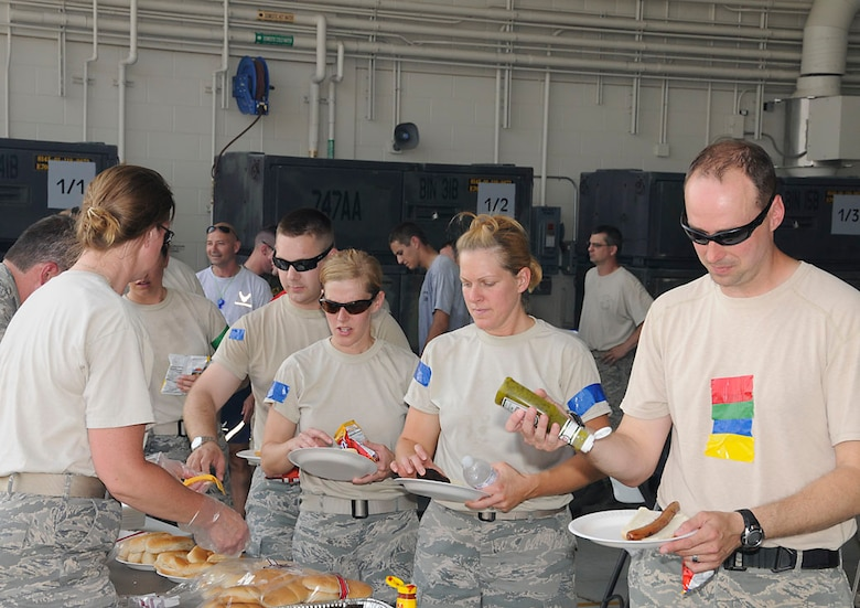 Security Forces Squadron participants, Staff Sgt. Brandon Criss, Tech. Sgt. Amber VanNess, Tech. Sgt. Jamie Renehan, and Staff Sgt. Rick Tryon (who appears to be neutral) flow through the chow line after working up an appetite on the battle field. Photo by Master Sgt. John M.  Day/Released