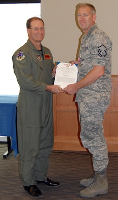 NELLIS AIR FORCE BASE, Nev. -- (Right) Master Sgt. Brian Marr, 926th Force Support Squadron force management superintendent, receives a meritorious service medal from Col. Herman Brunke, Jr., 926th Group commander, during a commander's call here June 29. Sergeant Marr is departing the 926th FSS soon for the Air Force Personnel Center in Denver, Colo., to be the superintendent of force development. (U.S. Air Force photo/Capt. Jessica Martin)