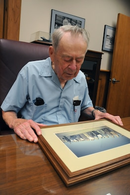 Captain Howard Ramstad (Ret.) reflects on a photograph taken by him of the original members of the 148th Fighter Wing. Capt. Ramstad, a founding member of the 148th Fighter Wing, was a pilot who flew the P-51 Mustang among other aircraft throughout his career.