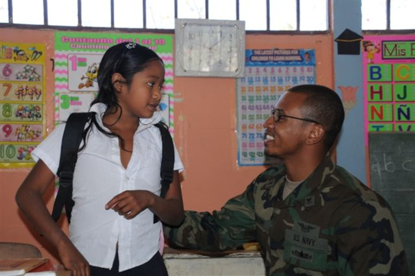 SOTO CANO AIR BASE, Honduras - Petty officer second class Paul Maestry, Joint Task Force-Bravo legal affairs, gives a student at Las Minitas a backpack from the Give a Kid a Backpack organization. More than 700 children in the surrounding Honduran communities received backpacks filled with school supplies Feb. 23 and 24.  (U.S. Air Force photo/Staff Sgt. Kimberly Rae Moore)