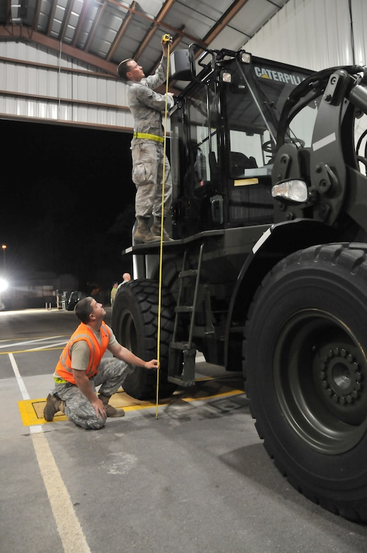 Staff Sgt. Andy Clyde (bottom), joint inspector from the 437th Aerial Port Squadron, and Senior Airman Michael Speaks, increment monitor from the 437 APS, measure the height of a Caterpillar loader during the mobility exercise Feb. 24 at Joint Base Charleston. The measurement ensured the equipment would fit into a C-17. (U.S. Air Force photo/Airman 1st Class Jared Trimarchi)