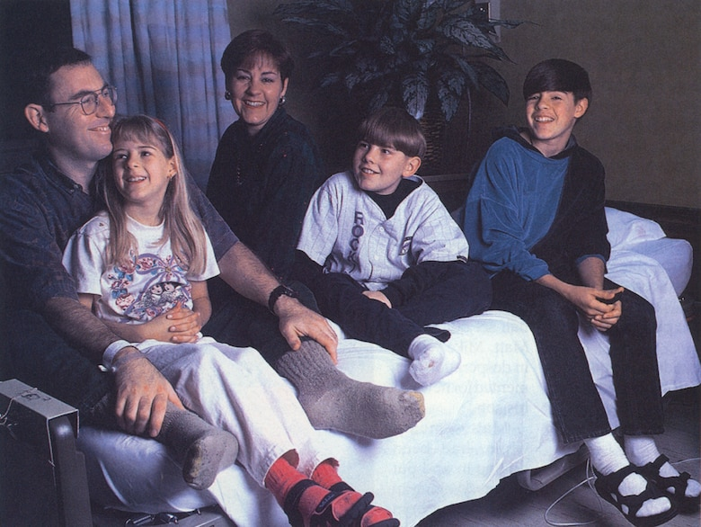 "MIRACLE ON THE MOUNTAIN - Surrounded by his family at Wilford Hall Medical Center in San Antonio, Mike still couldn't wear shoes after doctors had operated on his frostbitten feet. The family shared a laugh, recalling how Turkish tabloids claimed Mike was an American spy who took pills to sustain himself and used his son, Matt (center), as a cover up. In another instance, a prank caller claiming to be with freedom fighters said he had kidnapped the pair: ""You know things are bad when you would actually be relieved to find out your husband and son are in the hands of terrorists,"" Mary said. ""Because at least then you'd know they were alive."" (Photo by Rose Reynolds)"
