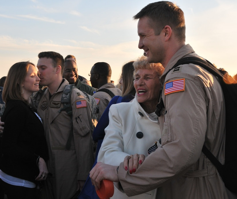 Capt. ZacharyCoburn (left) and Capt. Clark Grosvenor, pilots from the 16th AirliftSquadron, are greeted by their families March 3, after returning from adeployment to the Middle East. More than 130 Airmen from the 16 AS returnedhome from their 120-day deployment.