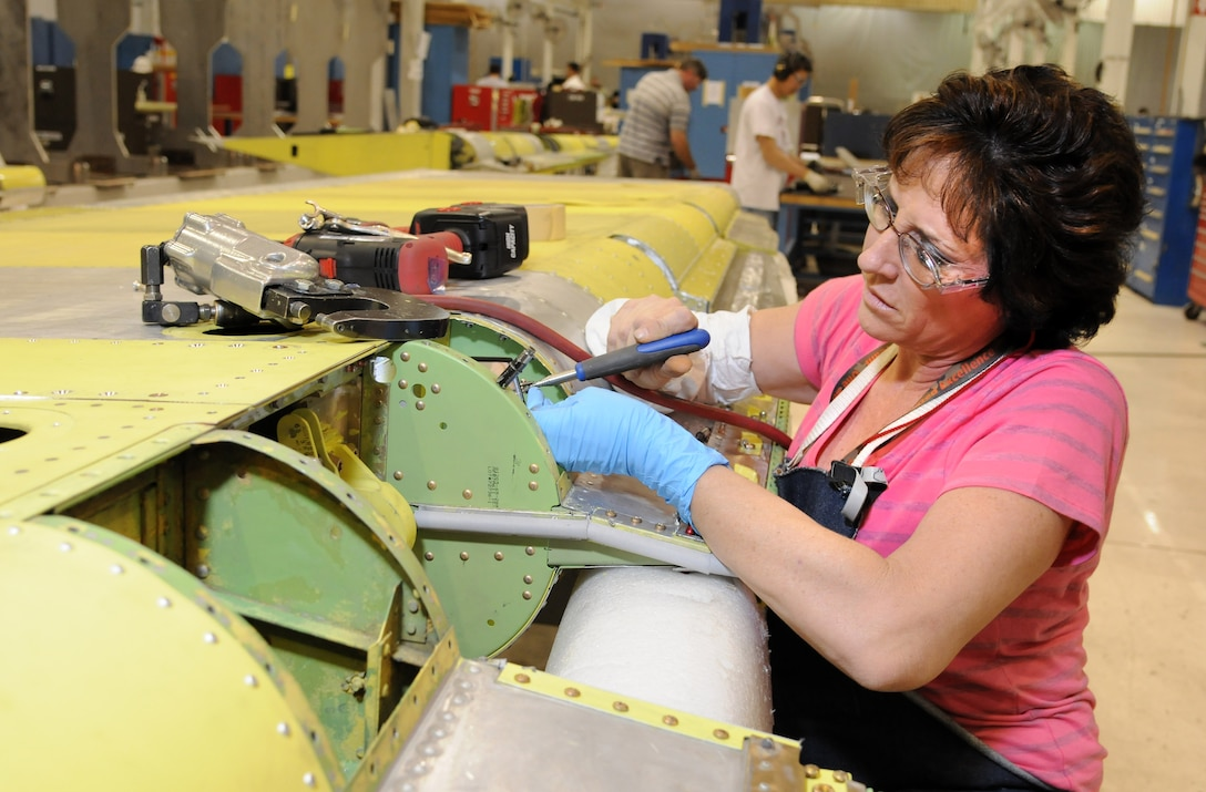 Linda Osborne, 551st CMMXS sheet metal mechanic, installs nut plates on a moon rib of a KC-135 rudder.  The KC-135 Rudder Shop is one of many production areas that the 551st CMMXS has implemented One-Piece Modular Flow Assembly Line improvements at Bldg. 9001. (Air Force photos by Dave Faytinger)