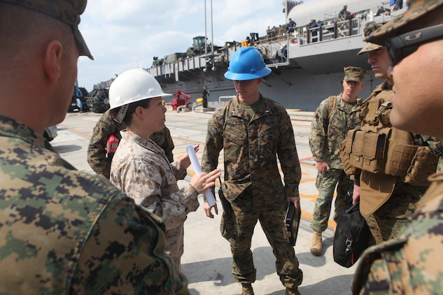 Chief Warrant Officer 2 Erin Patrick, Combat Cargo Officer, USS Harpers Ferry (LSD 49) (left), speaks with 1st Lt. Charles Breaux, team embarkation officer, 31st Marine Expeditionary Unit, regarding the movement of personnel and materials from the USS Denver (LPD 9) to the USS Harpers Ferry (LSD 49), March 4.  Elements of the 31st MEU switched ships mid-deployment allowing the MEU to remain ready to respond.  The transition comes midway through the MEU's scheduled deployment to the Asia-Pacific region, enhancing theater security and conducting bilateral training with multiple nations.  The 31st MEU is the U.S.'s only continually forward-deployed MEU, and remains a force-in-readiness in the Asia-Pacific region at all times.