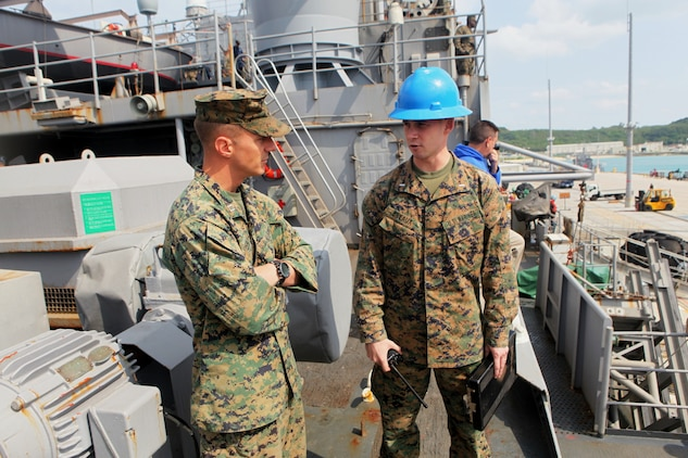 Capt. Pete Priester, commander of troops aboard the USS Denver (left), speaks with 1st Lt. Charles Breaux, team embarkation officer, 31st Marine Expeditionary Unit, regarding the movement of personnel and materials from the USS Denver (LPD 9) to the USS Harpers Ferry (LSD 49), March 4.  Elements of the 31st MEU switched ships mid-deployment allowing the MEU to remain ready to respond.  The transition comes midway through the MEU's scheduled deployment to the Asia-Pacific region, enhancing theater security and conducting bilateral training with multiple nations.  The 31st MEU is the U.S.'s only continually forward-deployed MEU, and remains a force-in-readiness in the Asia-Pacific region at all times.