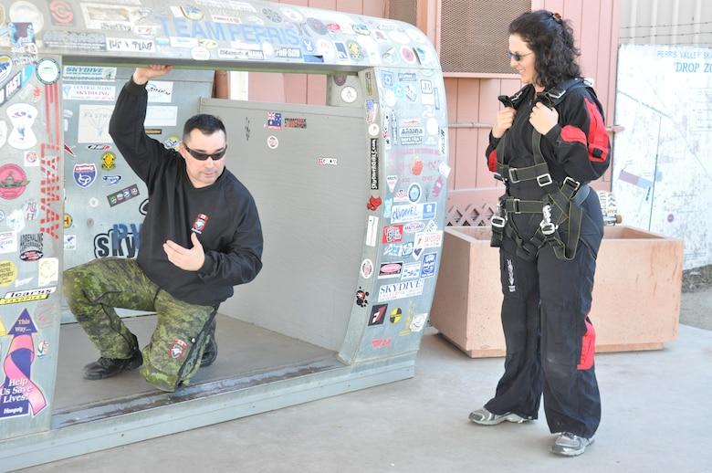 "SkyHawks jumpmaster, ""Scooter,"" similates skydiving movements as he prepares Linda Welz for her tandem jump.  (U.S. Air Force photo/ Megan Crusher)"