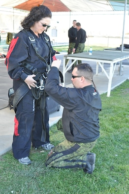 """SkyHawks jumpmaster, """"Scooter,"""" adjusts the straps on Linda Welz's harness before skydiving Feb. 11.  (U.S. Air Force photo/ Megan Crusher)"""