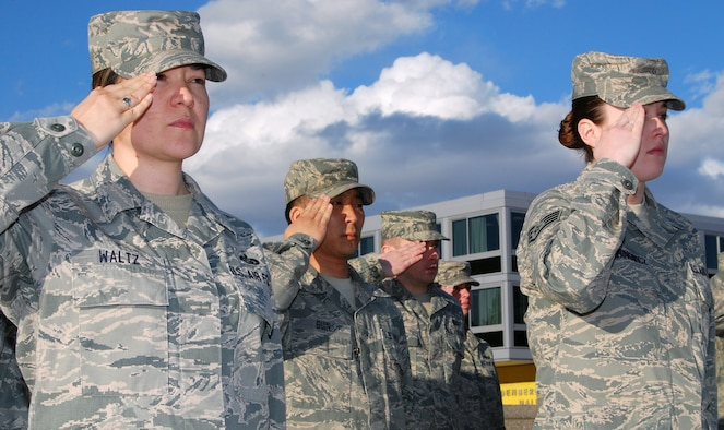 Tech. Sgt. Julie Waltz, left, and other Airmen stationed at the Air Force Academy observe retreat during a ceremony in the Terrazzo March 3, 2011. Sergeant Waltz is the NCO in charge of cadet classifications and assignments for the Academy's Directorate of Manpower and Personnel. (U.S. Air Force photo/Staff Sgt. Don Branum)