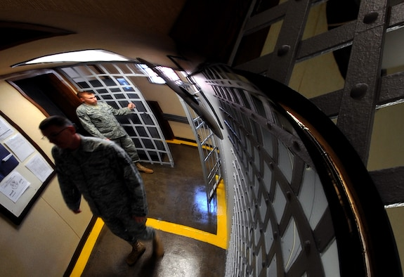 OFFUTT AIR FORCE BASE, Neb. - Staff Sgt. Andrew A. Blascyk, a confinement guard, and Tech Sgt. Raymond C. Kubiaczyk, NCO in charge of confinement for the 55th Security Forces Squadron, prepare to secure the temporary cell space gate on March 3. The facility is the oldest operational jail west of the Mississippi River and can house up to 15 inmates. U.S. Air Force photo by Jeff Gates