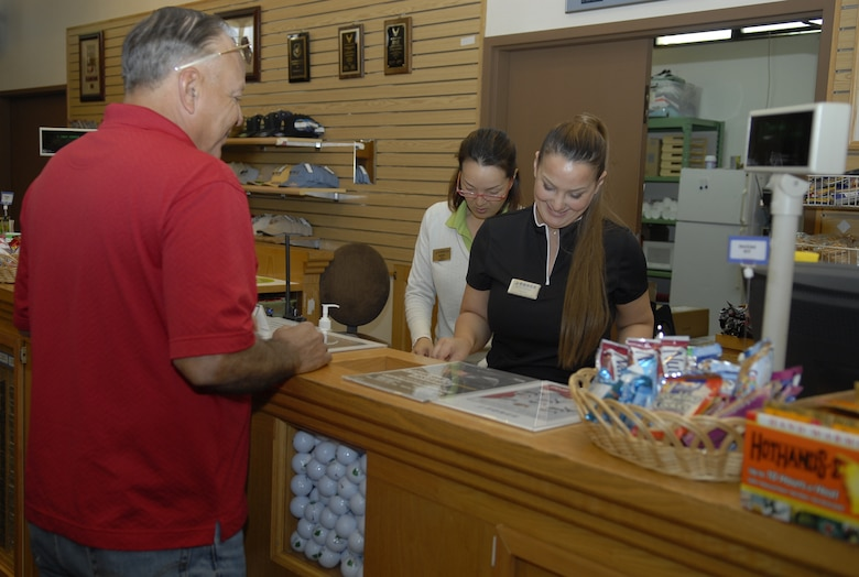 "Eloir Hirase and Runi Mori, cashiers at the Banyan Tree Golf Pro Shop, assist a customer before he begins a round of golf. Kadena's 18th Force Support Squadron earned one of three Air Force-wide ""5-star"" ratings in 2010 for superior programs and services. (U.S. Air Force photo/Airman 1st Class Tara A. Williamson)"
