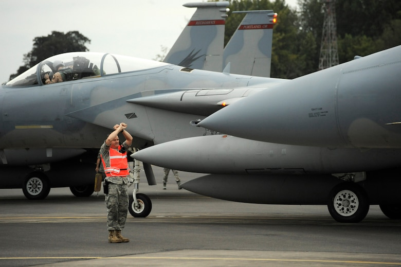 An Oregon National Guard Airman from the 142nd Fighter Wing marshals several F-15C Eagles at the Portland Air National Guard Base, Portland, Ore., on October 2nd, 2010. (U.S. Air Force photograph by Staff Sgt. John Hughel, 142nd Fighter Wing Public Affairs)