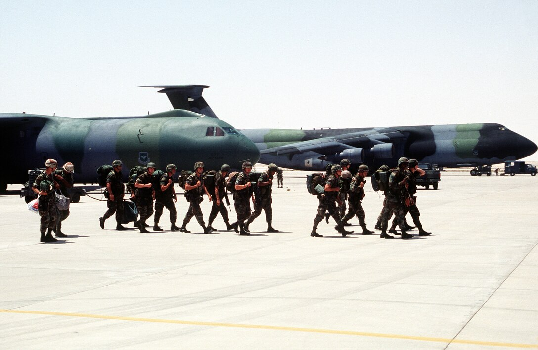 Troops cross the airfield after disembarking from Military Airlift Command C-141 Starlifter aircraft at a non-disclosed base in Southwest Asia in support of Operation Desert Shield in August 1990. (Department of Defense Photo)