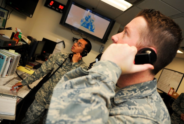 BUCKLEY AIR FORCE BASE, Colo. -- Senior Airman Joshua Carandang, 460th Space Wing Command Post, and TSgt Shane Hayes, 460th Space Wing Command Post checks through paper work on January 25, 2011.(U.S. Air Force photo by Airman 1st Class Paul Labbe.)