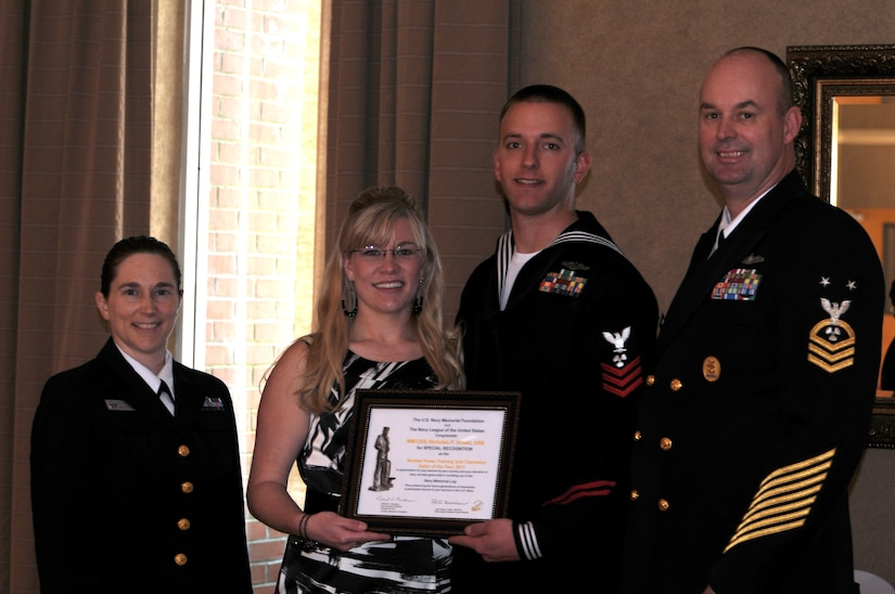 The Navy League Charleston recently honored local area Sailors of the Year at a ceremony held on Joint Base Charleston - Weapons Station. Pictured (left to right) after receiving his award are Lt. Cmdr. Erica Hoffman, executive officer of Nuclear Power Training Unit, Mrs. Howart, Machinist's Mate 1st Class Nicholas Howart, NPTU Sailor of the Year and Master Chief Petty Officer, Wayne Robbins, NPTU command master chief.