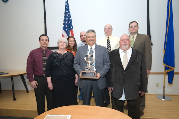 Edwards Civil Engineering Energy team members, (front row from left Dave Harrell, Amy Frost, Enrique Torres and Jack Frazier; Back row from left Minta Huddleston, Ron Ryan, James Judkins and Gerald Boetsch) pose for a picture with their new piece of hardware. The team received the Air Force Energy Conservation Award for its work in making the base more energy efficient and saving millions of dollars in the process. (Air Force photo by Rob Densmore)