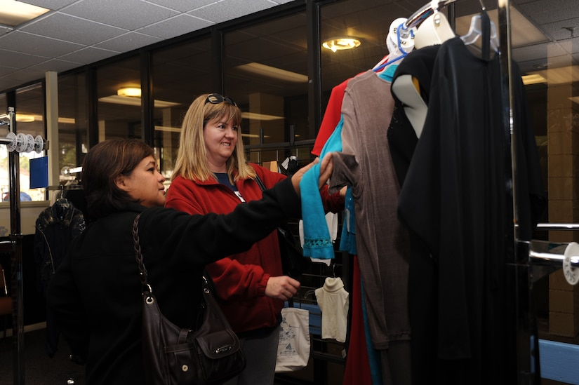 Maureen Robinson (left), wife of the 437th vice wing commander Col. Brian Robinson, and Cari Whitehill, wife of currently deployed 628th Comptroller Squadron commander Lt. Col. Trevor Whitehill, look at a dress during a leadership spouse preview of the on-base consignment shop March 7, at it's new location. The consignment shop will re-open March 8 and is now located next to the Air Base Youth Center. (U.S. Air Force photo/ Airman 1st Class Jared Trimarchi)