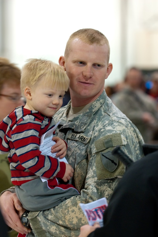 Army Sgt. Joshua Martin of Murray, Ky., a security force team leader for the Kentucky National Guard's Agribusiness Development Team III, holds his 3-year-old son, Gabriel, prior to the team's farewell ceremony March 4, 2011, at the Kentucky Air National Guard Base in Louisville, Ky. Team members are deploying to Afghanistan, where they will help Afghan farmers become agriculturally self-sufficient.  (U.S. Army photo by Staff Sgt. Aaron Hiler, 133rd Mobile Public Affairs Detachment)
