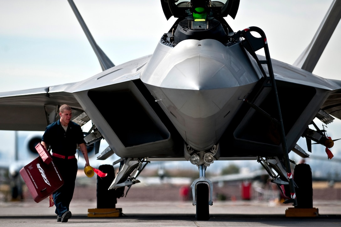 Airman 1st Class Jonathan Foster removes the intake covers from an F-22 Raptor March 2, 2011, before a Red Flag training mission at Nellis Air Force Base, Nev. Airman Foster is a crew chief assigned to the 49th Aircraft Maintenance Squadron at Holloman AFB, N.M. (U.S. Air Force photo/Tech Sgt. Michael R. Holzworth)