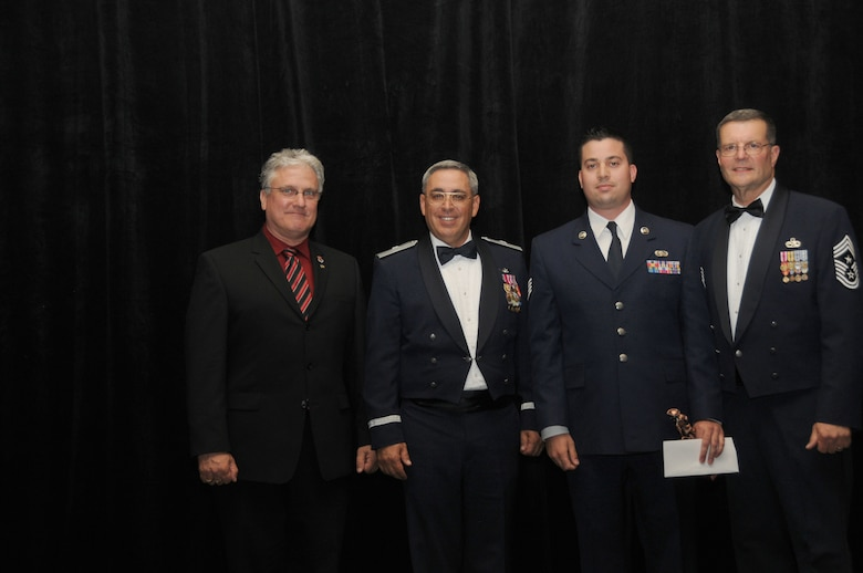 Staff Sgt. Travis Casey from the 107th Air Control Squadron, Phoenix Ariz, is the Arizona Air National Guard's Command Chief Master Sergeant Award winner. Sergeant Casey accepts his award from Mr. Glenn Klassen, President, Arizona National Guard Patriots, Brig. Gen. Michael Colangelo, Commander, Arizona Air National Guard and Chief Daniel Irving, Arizona State Command Chief on Saturday March 5, 2011.  (U.S. Air Force photo by Airman 1st Class Rashaunda Williams/Released)