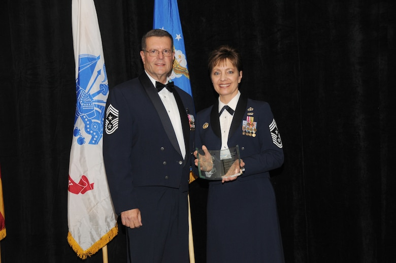 Chief Master Sgt. Dan Irving, Arizona State Command Chief, presents guest speaker Chief Master Sgt. Denise Jelinski-Hall a plaque of appreciation during the Airmen of the Year Banquet at the Chaparral Suites and Resorts in Scottsdale Ariz, Saturday, March 5, 2011. Chief Jelinski-Hall is the Senior Enlisted Leader for the National Guard Bureau. (U.S. Air Force photo by Airman 1st Class Rashaunda Williams/Released)