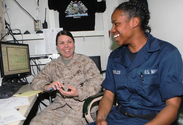 Chief Warrant Officer 2 Erin Patrick, combat cargo officer aboard the USS Harpers Ferry (LSD 49), of Mesick, Mich., talks about tax preparation with Seaman Ronika Peeples, of New Orleans, La., March 11.  As the CCO, Patrick coordinates the loading, storage, and offloading of all 31st Marine Expeditionary Unit equipment on ship.  Patrick has been deployed 18 of the last 24 months, away from her husband and four children.  She is one of the Marine Corps' many professionals who sacrifice time with family to serve their country.  While deployed, Patrick mentors junior service members.