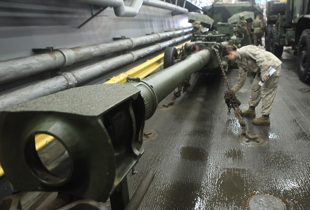Chief Warrant Officer 2 Erin Patrick, combat cargo officer aboard the USS Harpers Ferry (LSD 49), stands atop vehicles and equipment of the 31st Marine Expeditionary Unit March 11.  As the CCO, Patrick coordinates the loading, storage, and offloading of all 31st MEU equipment on ship.  Patrick has been deployed 18 of the last 24 months, away from her husband and four children.  She is one of the Marine Corps' many professionals who sacrifice time with family to serve their country.
