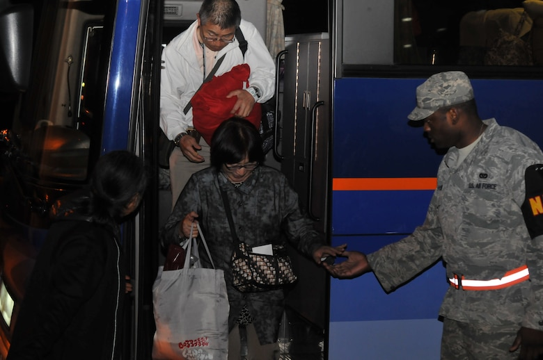 YOKOTA AIR BASE, Japan -- Mr. Suzuki Hideto, 374th Force Support Squadron recreational specialist, and Staff Sgt. Jason Holmes, 374th Civil Engineer Squadron, assist a passenger exiting a bus here March 11. The passengers arrived to the base after their commercial flights were diverted from Narita International Airport, Tokyo, Japan, due to an earthquake that struck near Tokyo. (U.S. Air Force photo/Airman John D. Partlow)
