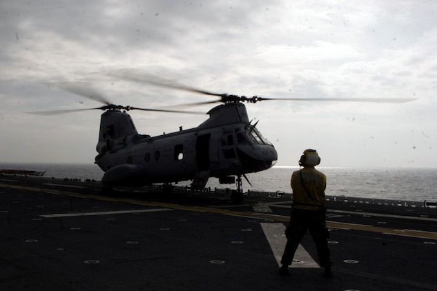 A Sailor with Amphibious Squadron 11 waits to direct a CH-46E Sea Knight helicopter with Marine Medium Helicopter Squadron 262 (reinforced), 31st Marine Expeditionary Unit, during flight deck operations, March 13. Marines and sailors of the 31st MEU aboard the USS Essex (LHD 2) are making preparations for potential humanitarian assistance and disaster relief efforts after an 8.9 earthquake and subsequent tsunami struck Japan causing widespread damage. The USS Essex and 31st MEU are heading for the northeast coast of Japan to be ready to support to our friends and allies in their ongoing efforts and to be near enough to provide that support if called upon.