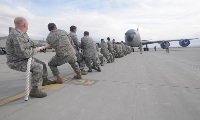 """Members of the 151st Air Refueling Wing pull a KC-135 Stratotanker in a"""" Plane-Pull"""" competition as part of Winter Wingman Day, March 12, 2011, at the Utah Air National Guard base in Salt Lake City. Teams competed to see who could pull the 120,00+ pound aircraft over a 40 feet distance in the shortest time. (U.S. Air Force photo by Master Sgt. Gary J. Rihn)(RELEASED)"""
