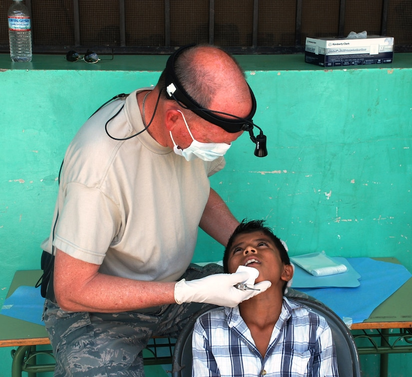 SOTO CANO AIR BASE, Honduras - Lt. Col. Thompson Lanius, Joint Task Force-Bravo Medical Element Dental Services officer, performs a routine dental check on a patient in Choluteca Mar. 11.  Colonel Lanius was part of a Medical Readiness and Training Exercise held there to assist the Honduran Ministry of Health in providing basic medical services to residents of the area.  JTF-Bravo routinely conducts training exercises throughout Central Americal to ensure regional stability as well as to our ability to respond to natural disasters, provide humanitarian assistance, and protect the vital interests of the United States. (U.S. Air Force photo/Capt. John T. Stamm)