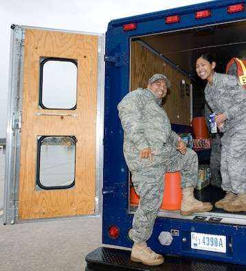 """Chaplain (Capt.) Richard Rojas visits Airman 1st Class Rossmery Holyfield, 436th Medical Operations Squadron medical technician, in the iconic """"Holy Roller"""" van at Dover Air Force Base, Del. The base chapel staff has spent more than 4,000 hours visiting members of Dover AFB and the community. (U.S. Air Force photo by Jason Minto)"""