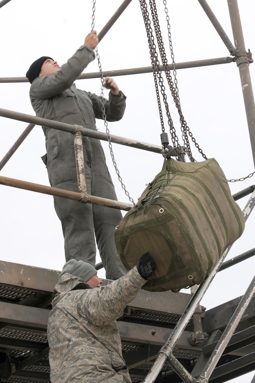 Airman 1st Class Justin Foster, 20th Aircraft Maintenance Squadron crew chief, works the chains on a B-52 Drag Chute Maintenance Stand as Tech. Sgt. Tobin Young, a 707th Maintenance Squadron crew chief, guides a drag chute up for replacement in a 2nd Bomb Wing B-52H that has just returned from a nuclear training mission at Barksdale Air Force Base, La, March 5, 2011. The 707th MXS is an Air Force Reserve classic associate unit assigned to the 2nd Maintenance Group and supports the 343rd Bomb Squadron. The launch of this crew and aircraft was significant for being the first supported by 2nd BW operations and maintenance personnel during a 307th Bomb Wing Reserve Unit Training Assembly. (U. S. Air Force Photo/Master Sgt. Greg Steele)