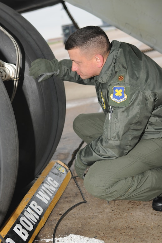 Maj. Jimmy Jackson, a 343rd Bomb Squadron instructor pilot, inspects the landing gear of a B-52H bomber as part of his pre-flight checks before mission takeoff at Barksdale Air Force Base, La, March 5, 2011. The mission simulated the release of both nuclear Air Launched Cruise Missiles and gravity bombs. The launch of this crew and aircraft was significant for being the first supported by 2nd Bomb Wing operations and maintenance personnel during a 307th Bomb Wing Reserve Unit Training Assembly. The 343rd BS is a classic associate unit assigned to the 2nd BW. (U. S. Air Force Photo/Master Sgt. Greg Steele)