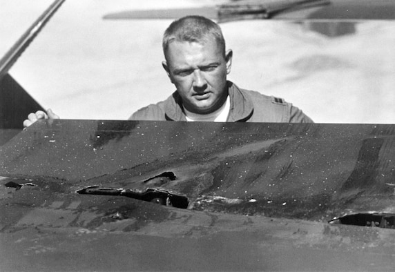 Misty FAC Capt. Ted Powell examines his battle-damaged F-100F. (U.S. Air Force photo)